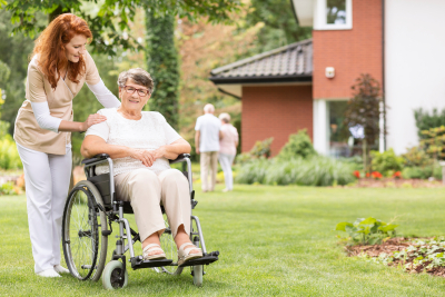 professional female caregiver with her patient in the garden